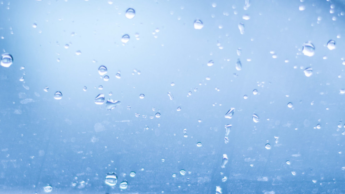 Drops of condensation on a window with a blue background